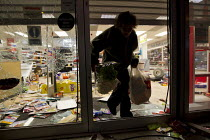 08-08-2011 - Somerfield is looted, person carries out flowers. Riots spread to Crydon following a fatal police shooting. Riot police struggle to maintain order as rioting spreads across the country after Mark Dugg... © Jess Hurd