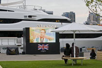 11-08-2012 - A handful of spectators watch a big screen TV the end of the athletics in a prepared spectator area where the super-yatchs are moored. The Seanna, is one of the Super-yatchs moored at Canary Wharf for... © Jess Hurd
