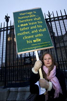 15-02-2013 - Anti Gay rights campaigner with a placard quote on marriage from Genesis 2:24 in the Old Testament: Therefore shall a man leave his father and his mother, and shall cleave unto his wife
