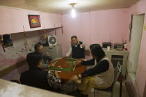 13-10-2013 - Men play Mahjong, a game with dominos or tiles. Jiaochangkou Hutong is a traditional courtyard residence, most of which are being demolished to make way for new roads and gentrified property developme... © Jess Hurd