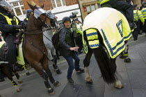01-02-2014 - Video journalist Jason Parkinson dodges riot police horses as anti fascists demonstrate in Slough against the English Defence League. © Jess Hurd