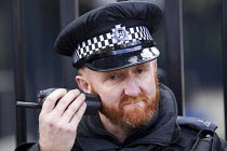 25-02-2015 - Downing Street police officer with his radio Westminster, London © Jess Hurd