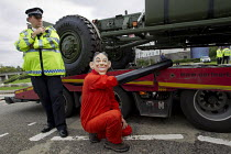 07-09-2015 - Stop DSEi arms fair protest prevents military vehicle entering ExCel centre London Stop Arming Israel. Defence Security and Equipment International exhibition, protester with a Tony Blair mask locked... © Jess Hurd