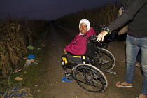 20-09-2015 - Woman with amputated legs has her wheelchair pushed through the corn fields as refugees make their way to Europe via Tovarnik, Croatia border crossing. Serbia. © Jess Hurd
