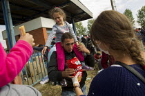 22-09-2015 - A volunteer gives food to exhausted refugees wait to access the overcrowded Opatovac refugee camp. Croatia. © Jess Hurd
