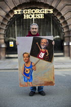 10-04-2015 - Artist Kaya Mar with satirical painting of Cameron & Corbyn TUC march against austerity cuts and unfair Trade Union Bill, Conservative Party Conference, Manchester. © Jess Hurd