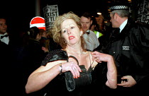 04-12-1999 - Flustered rich woman attempts to get through the Miss World protest to view the contest. Protesters pelted people going into the Kensington Olympia with eggs and flower, burnt Barbie dolls and copies... © Jess Hurd