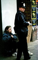 10-12-1999 - Police officer taking the details of a homeless man, London Surveillance for operation Clean-Up initiative from the Homeless Tsar 1999 © Jess Hurd