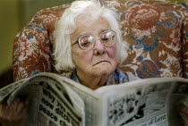 20-02-1996 - Elderly woman sitting in an armchair, reading a newspaper. © Paul Carter
