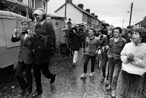12-07-1985 - RUC preventing loyalist march from passing along traditional route through catholic area, Portadown, Northern Ireland 1985. Young catholics jeer as loyalist band member is arrested. © John Sturrock