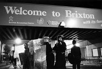 28-09-1985 - Riot Police occupy Brixton Road 1985 below a Welcome to Brixton sign after rioting broke out in protest at police shooting of innocent black woman, Dorothy Cherry Groce. © John Sturrock
