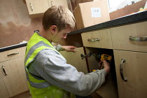 17-03-2010 - Apprentice working towards his NVQ level 2 in carpentry and joinery. Installing a kitchen unit whilst working for the Nottingham City Homes, One In A Million Scheme. © Justin Tallis