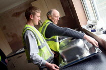 17-03-2010 - Apprentice working towards his NVQ level 2 in carpentry and joinery. Being helped to install a kitchen sink by an older worker whilst working for the Nottingham City Homes, One In A Million Scheme. © Justin Tallis