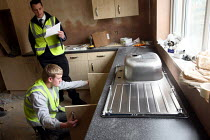 17-03-2010 - Apprentice working towards his NVQ level 2 in carpentry and joinery. Installing a kitchen unit and being watched by a supervisor whilst working for the Nottingham City Homes, One In A Million Scheme. © Justin Tallis