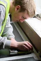 17-03-2010 - Apprentice working towards his NVQ level 2 in carpentry and joinery. Measuring up the space where he will install a kitchen sink whilst working for the Nottingham City Homes, One In A Million Scheme. © Justin Tallis