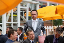 29-07-2010 - Racegoer with a couple of bottles at Venue Cliquot champagne bar. Goodwood racecourse. © Justin Tallis