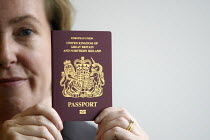 25-08-2010 - Sarah Rapson, chief executive of the Identity and Passport Service posing with a specimen of the newly designed UK passport during unveiling at the Passport Office in London. © Justin Tallis