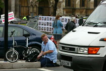 10-06-2009 - A man laughing as he pumps up a flat tire in the middle of the road. RMT tube strike, London. © Justin Tallis