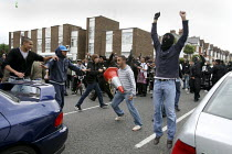11-09-2009 - Muslim youths shout and throw bottles at police who are protecting the English Defence League demonstrators after scuffles broke out near Harrow mosque. London. © Justin Tallis