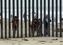03-07-2011 - San Ysidro, California, children looking through the fence at Border Field State Park separating the USA and Mexico at a beach at the Pacific Ocean © Jim West