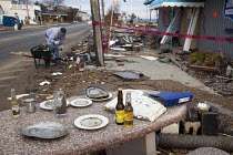 28-11-2012 - Union Beach, New Jersey - A man cleans up outside Jakeabobs Bay waterfront restaurant, which was heavily damaged by Hurricane Sandy. Someone has set an outdoor table with items salvaged from the storm... © Jim West