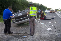 25-07-2013 - Falfurrias, Texas - A deputy sheriff and a state trooper making notes after a van holding 26 undocumented immigrants from Central America overturned on Texas Highway 285. The driver had picked up the... © Jim West