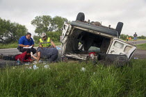 25-07-2013 - Falfurrias, Texas - A deputy sheriff and a state trooper look on while a passing motorist treats an injured man after a van holding 26 undocumented immigrants from Central America overturned on Texas... © Jim West