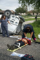25-07-2013 - Falfurrias, Texas - An EMT treats an injured man after a van holding 26 undocumented immigrants from Central America overturned on Texas Highway 285. The driver had picked up the migrants just down th... © Jim West