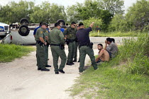 25-07-2013 - Falfurrias, Texas - U.S. Border Patrol officers and a deputy sheriff question undocumented immigrants from Central America found hiding after a van holding 26 migrants crashed and overturned on Texas... © Jim West