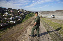 27-01-2012 - San Ysidro, California, U.S. Border Patrol agent Joe Velasquez in the area between the old and new border fence between the USA and Mexico. A Tijuana neighborhood is across the old fence. © Jim West