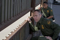 27-01-2012 - San Ysidro, California,U.S. Border Patrol agents Jerry Conlin (L) and Joe Velasquez look through an opening in the border fence separating the USA and Mexico © Jim West