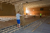 04-08-2015 - Detroit, Michigan Volunteers from Life Remodeled, a nonprofit organization, installing a new floor in the Osborn High School gym in an effort to renovate the school and improve the surrounding neighbo... © Jim West