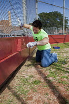 08-04-2015 - Detroit, Michigan Volunteers from Life Remodeled, a nonprofit organization, painting the baseball ground at Osborn High School in a community improvement project. © Jim West