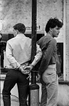 09-04-1984 - Striking miners handcuffed to a lamp post, 1984 Cresswell colliery, Derbyshire when 5,000 miners turned out to a mass picket. Police arresting young miners © Peter Arkell