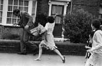 09-07-1984 - Miners wife attacking a scab with her shoe, Miners Strike 1984 making the opinion of the community clear after police invaded the pit village of Rossington near Doncaster, South Yorkshire © Peter Arkell