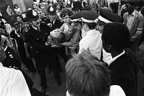 28-08-1977 - Notting Hill Carnival 1977. Person injured in the riots being rushed to an ambulance © Peter Arkell