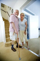 10-08-2009 - A disabled man and his wife laugh after he makes it down the stairs. The man has had his leg amputated due to poor blood circulation. © Paul Box