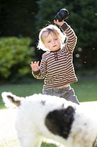 25-05-2014 - A toddler plays in a garden, with his dog, Stratford Upon Avon. © Paul Box