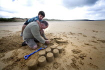 20-08-2009 - A young boy and his father making a sandcastle, Freshwater West beach in Pembrokeshire. © Paul Box
