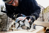08-02-2010 - A carpenter cuts the oak A-frames for a barn conversion. © Paul Box
