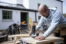 15-05-2010 - A carpenter using a router to make kitchen cabinets at a farm house renovation. © Paul Box