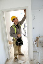 22-03-2012 - A carpenter working fitting a door frame, new housing near Taunton, Somerset. © Paul Box