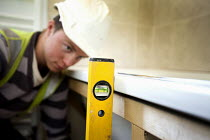 22-03-2012 - A carpenter fitting a bath, new housing near Taunton, Somerset. © Paul Box