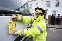17-06-2015 - Residents protesting at new resident parking scheme, St Pauls, Bristol. A protestor dressed as a parking attendant issuing mock parking tickets. © Paul Box