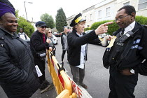 17-06-2015 - Sharing a joke with the police as residents protesting at new resident parking scheme, St Pauls, Bristol. A protestor dressed as a parking attendant issuing mock parking tickets. © Paul Box