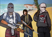 27-08-2015 - Dismaland a parody of Disneyland theme park by Banksy, Weston Super Mare. Boy with his head through the hole in a seaside stand in life size cutout of Masked Somali pirates holding AK47 infront of a f... © Paul Box