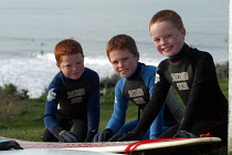 12-02-2004 - Ginger haired brothers wax surfboard before going surfing at Woolacombe in Devon © Paul Box