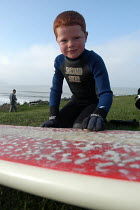12-02-2004 - Ginger haired boy waxs surfboard before going surfing at Woolacombe in Devon © Paul Box