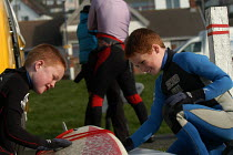 12-02-2004 - Ginger haired boys wax surfboard before going surfing at Woolacombe in Devon © Paul Box