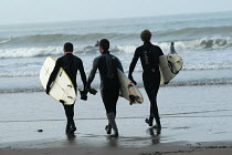 12-02-2004 - Three friends walk down the beach with surfboards, Woolacombe in Devon © Paul Box